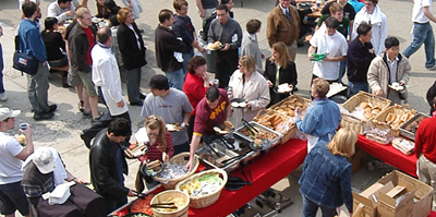 photo of people surrounding picnic tables full of food